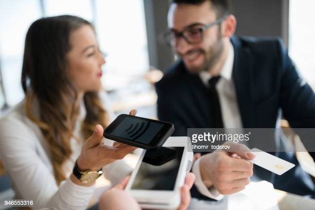 Office lady using smart phone to pay for meal