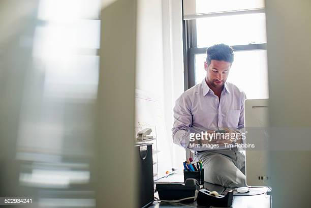Office life. A man checking his phone in an office.