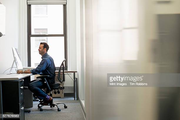 Office life. A man in casual clothing seated at a desk looking at a computer screen.
