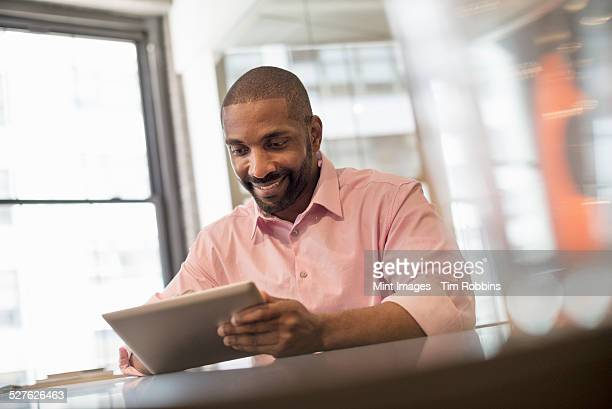 office life. a man seated at a desk using a laptop computer. - rolled up sleeves stock pictures, royalty-free photos & images