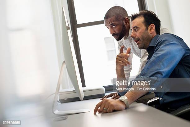 Office life. Two men at a desk looking at a computer.