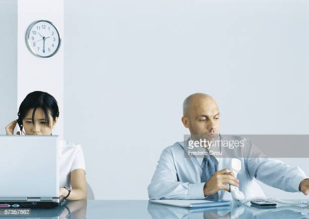 office, man holding telephone while woman uses computer - side by side stock photos and pictures