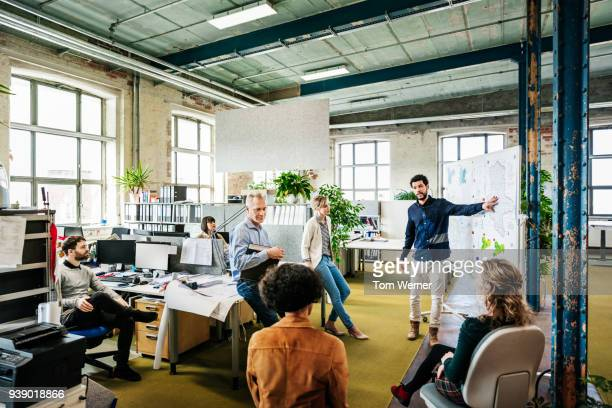 office manager addressing his team during morning meeting - werkplek stockfoto's en -beelden