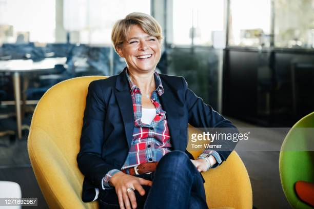 office manager sitting in green chair smiling - businesswoman stock pictures, royalty-free photos & images