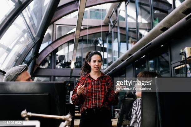 office manager talking to her team - schottenkaro stock-fotos und bilder