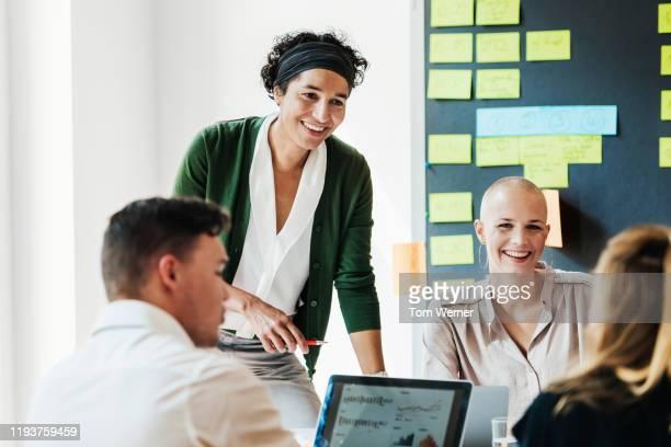 office manager talking to team during meeting - begrippen en thema's stockfoto's en -beelden