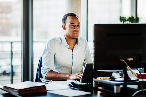 Office Manager Working On Computer At His Desk 1053499704