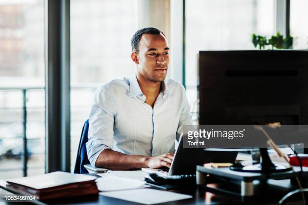 office manager working on computer at his desk - men stock pictures, royalty-free photos & images