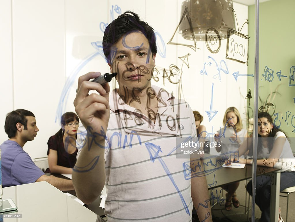 Office manager writing information on glass wall : Stock Photo