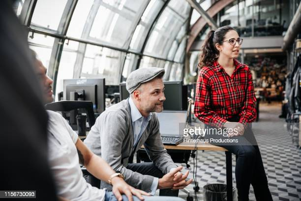 office managers listening during morning meeting - plaid shirt stock pictures, royalty-free photos & images
