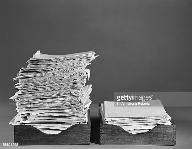 1960s: Office paper trays, In tray overflowing, Out tray with smaller pile.