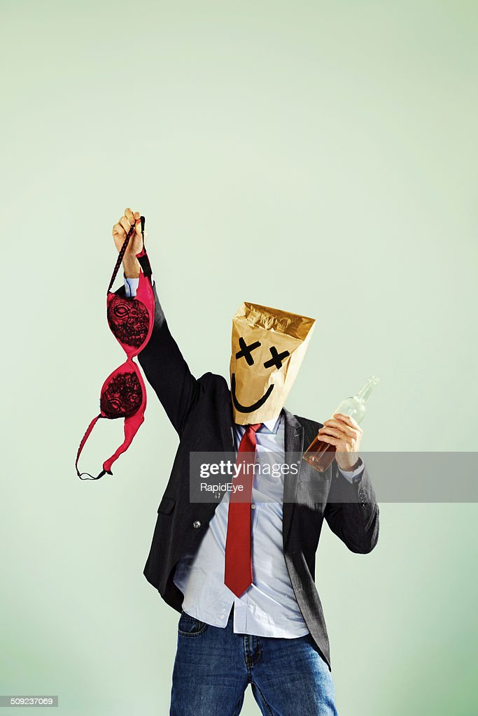 Office party drunk in paper-bag mask waving bra : Stock Photo