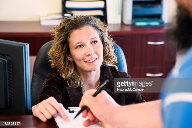 office receptionist getting signature from visitor - register stock photos and pictures