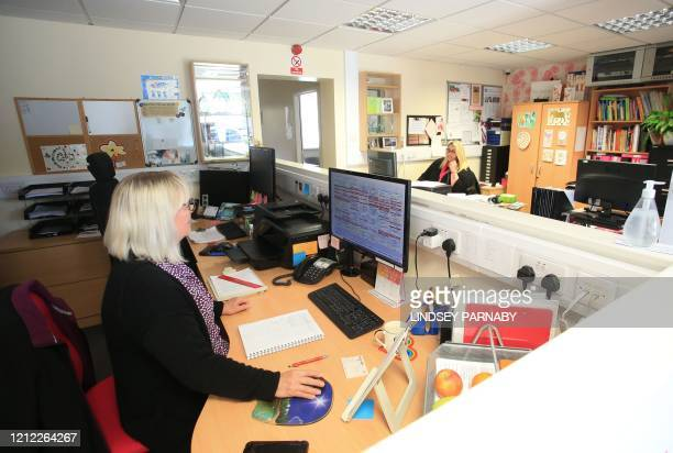 Office staff members of Elite Care Solutions Ltd observe social distancing during work at their base in Scunthorpe, northern England on May 7, 2020....
