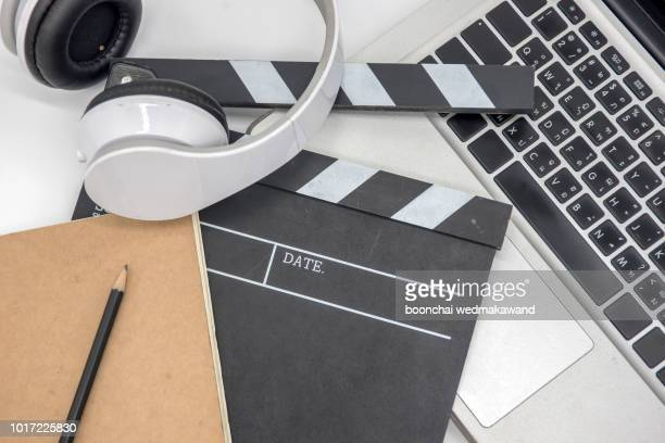 office stuff with movie clapper laptop and coffee cup pen notepad on the wood table top view shot.dark effect - producer stock pictures, royalty-free photos & images