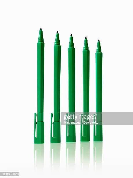 Office supplies. Green coloured pens, felt nibs and pen top cases, arranged in a row.