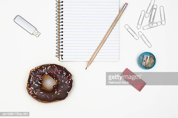Office supply and doughnut on desk, overhead view