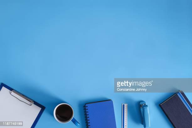 office supply items on blue work desk - ブツ撮り ストックフォトと画像
