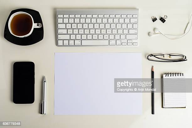 office table top view shot with keyborad, tea cup, mobile phone, eye glasses, pen, pencil, ear phone with blank space for your content - multimedia stock pictures, royalty-free photos & images