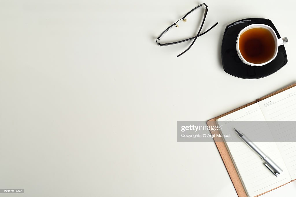 Office Table Top View Shot With Tea Cup, Notebook, Eyeglass And Pen With  White