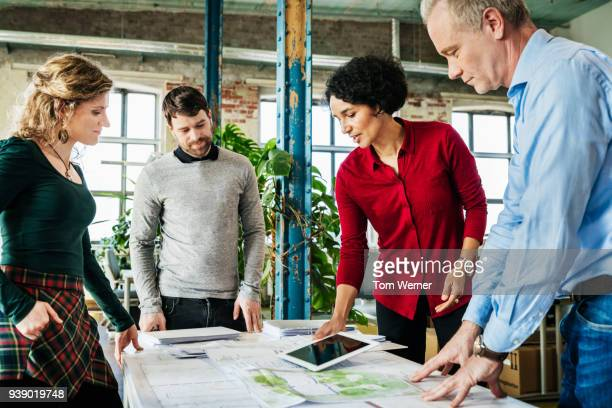 Office Team Looking Over Documents During Meeting