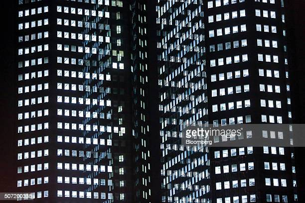 Office windows sit illuminated inside the twin tower skyscraper headquarters of Deutsche Bank AG at night in Frankfurt Germany on Wednesday Jan 27...
