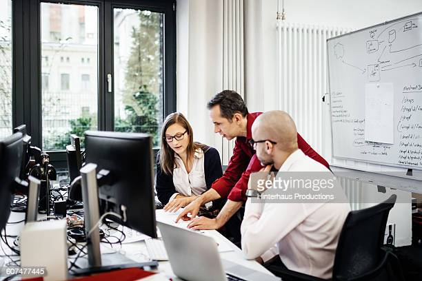 Office with three colleagues working at a desk.