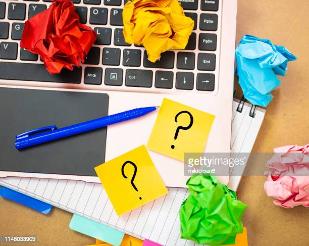 office work with laptop and sticky notes with question mark - asking stock pictures, royalty-free photos & images