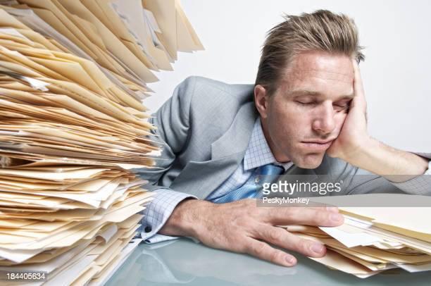Büroberuf Geschäftsmann beim Einschlafen in Haufen von Datei-Ordner