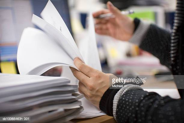 office worker checking documents on desk, mid section, side view - pilha arranjo imagens e fotografias de stock