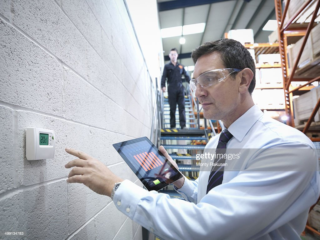 Office worker checking thermostat in factory : Stock Photo