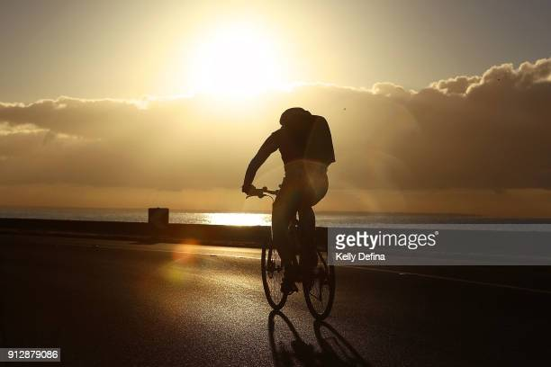 Office worker cycles toward Melbourne City after sunrise on a hot summer's day at Altona Beach on December 20 2017