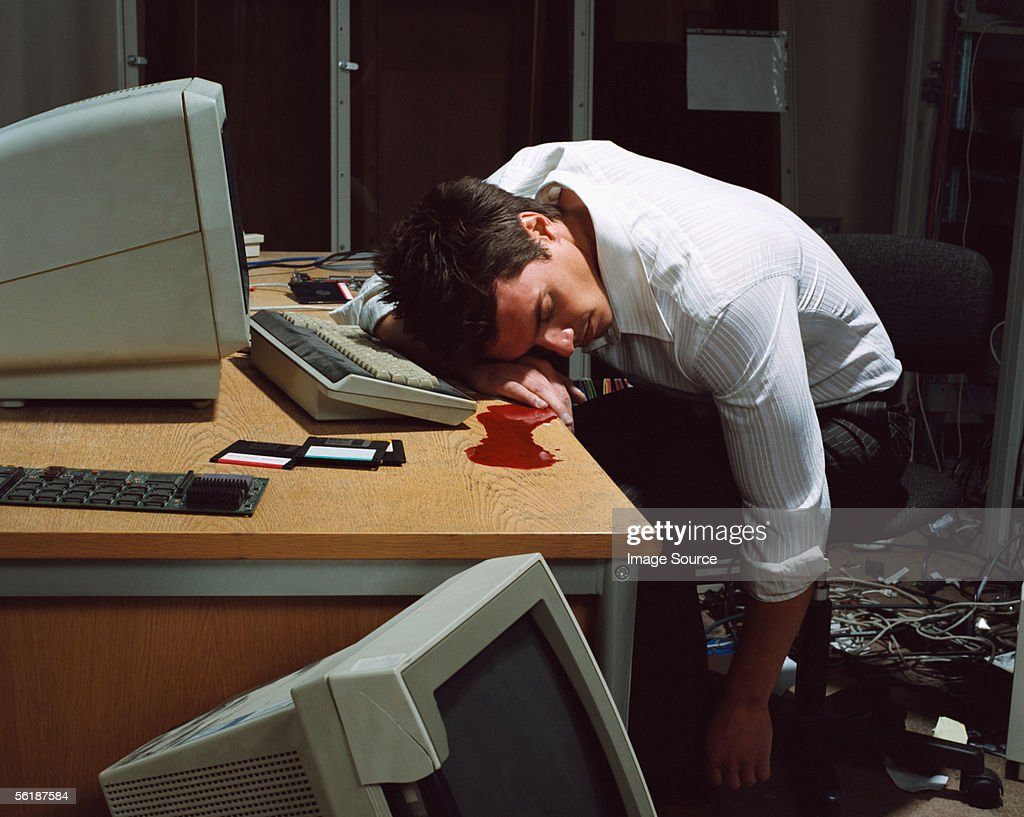 Office worker dead at his desk : Stock Photo