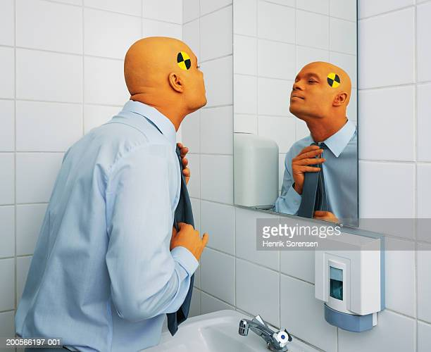 Office worker dressed as crash test dummy adjusting tie in bathroom