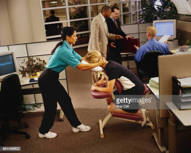 office worker getting chair massage - black massage therapist stock photos and pictures