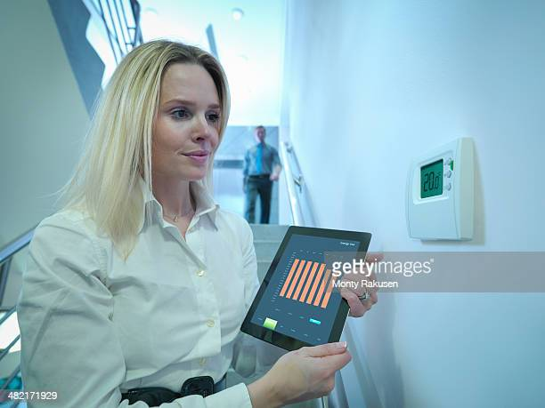 Office worker holding digital tablet next to office thermostat in stairwell