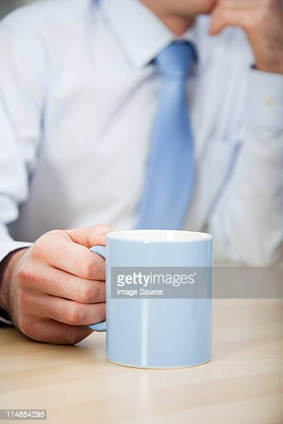 Office worker holding mug, close up