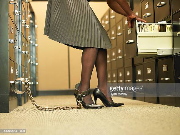 Office worker in archives with chained to filing cabinet, low section
