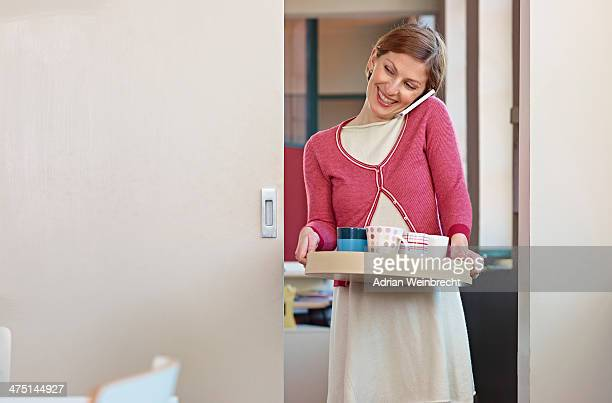 Office worker on cell phone, carrying tea tray