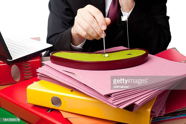 office worker playing miniature golf on desk with folder stacks - wasting time stock pictures, royalty-free photos & images