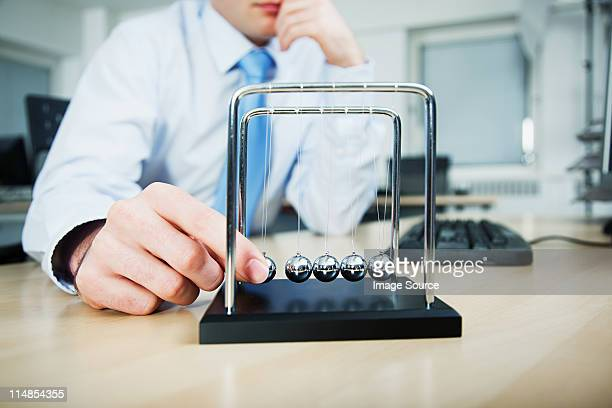 office worker playing with newtons cradle - wasting time stock pictures, royalty-free photos & images