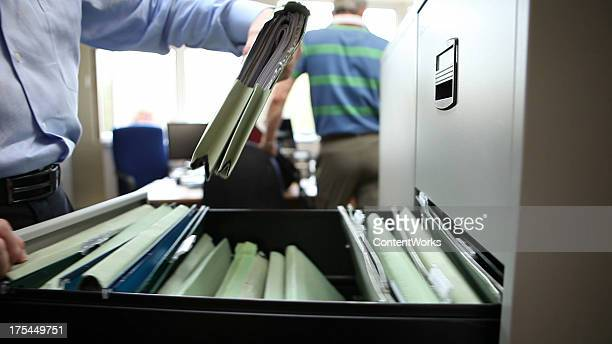 Office worker retrieves file from filing cabinet