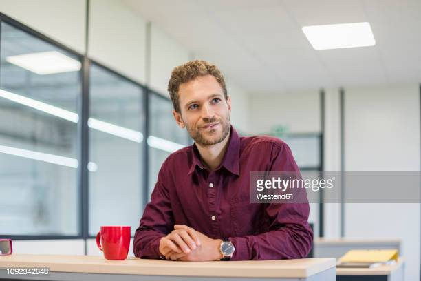 office worker sitting at desk with red coffee cup - employee appreciation stock pictures, royalty-free photos & images