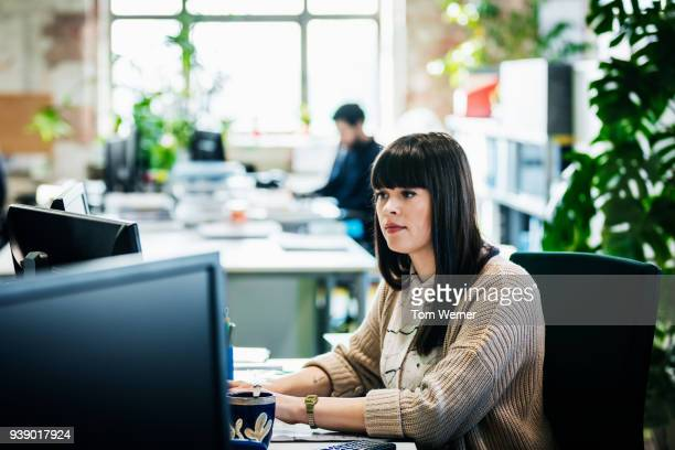 office worker sitting at her desk - look familiar stock pictures, royalty-free photos & images