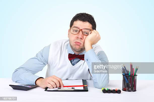 Office worker sitting in office and making boring face