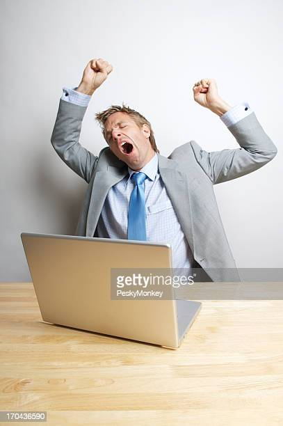 Office Worker Stretches and Yawns at His Desk
