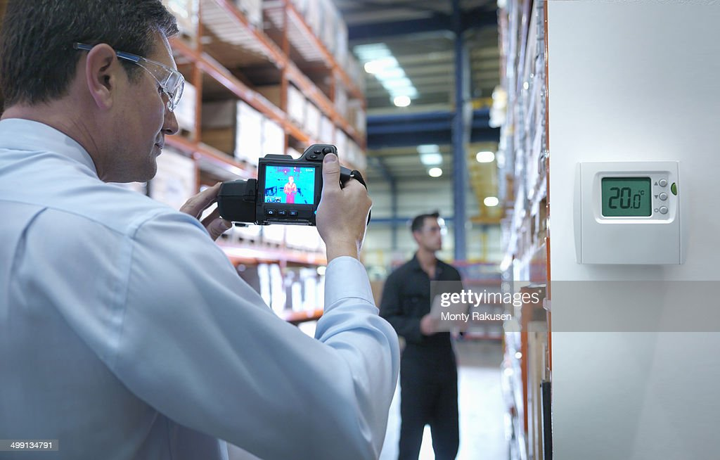 Office worker taking thermal image with camera in factory next to thermostat : Stock Photo