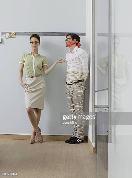 office worker tied up with ropes in corner - women dominating men stock photos and pictures