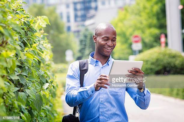 Office worker walking back home smiling while looking at tablet