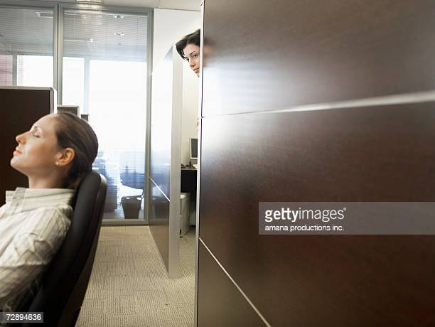 office worker watching co-worker sleeping - lech stock pictures, royalty-free photos & images